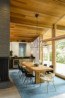 As you can see above, the original brick of the fireplace is now exposed, highlighting the warmth of the cedar ceilings. The dining room connects the living room/kitchen and overlooks the terrace, giving the home a strong sense of the outdoors.