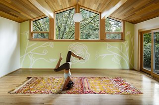 With the addition of wood ceilings and sliding doors that lead out to the garden, the former dark home office is now a bright and airy yoga studio for the homeowner where she teaches and practices daily.
