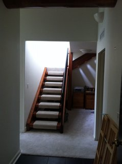 A look at the stairway leading upstairs. The wall was removed during the renovation to open up the space and expose it to the living room area.