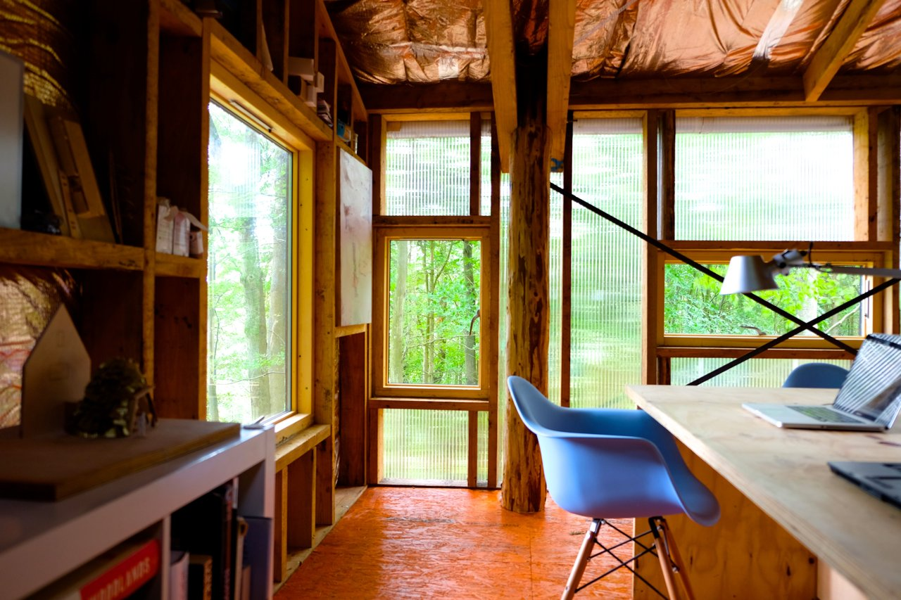 Office, Study Room Type, Bookcase, Chair, Plywood Floor, Desk, and Lamps Visible Studio is heated by waste wood from the woodland, and water from the roof feeds into an attenuation pond that forms a natural habitat.  Photo 11 of 26 in 10 Buildings We Love by Piers Taylor