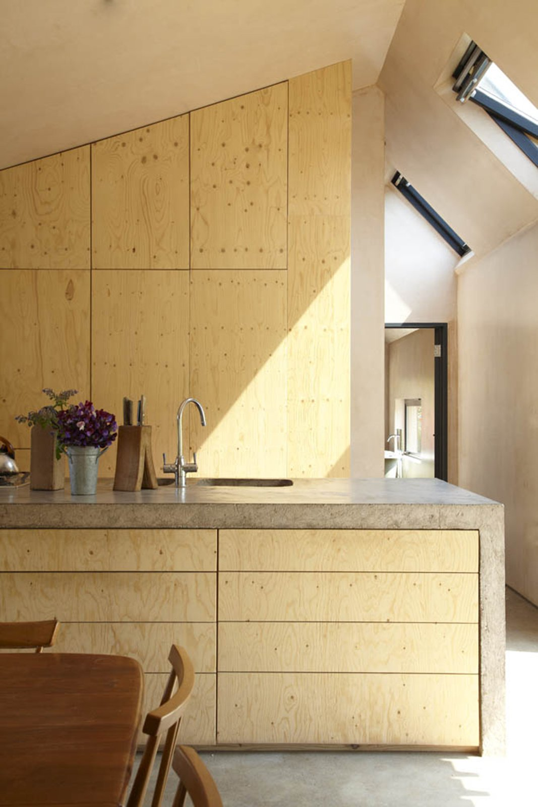 Kitchen, Granite Counter, Drop In Sink, Wood Cabinet, Concrete Floor, and Concrete Counter The minimalist interiors showcase the simple material palette.  Photo 17 of 26 in 10 Buildings We Love by Piers Taylor