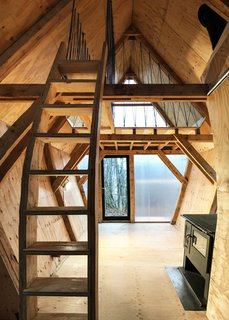"All of the joinery is crafted from plywood offcuts, including the two staircases. Handrails are made from offcuts of blue rope, leftovers from Invisible Studio's Studio in the Woods program. Both gable ends, ""glazed"" with high-performance interlocking polycarbonate, afford lots of light."