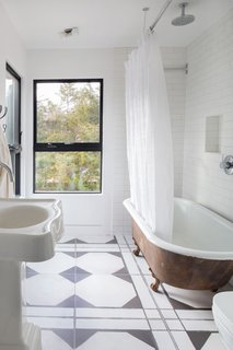 A clawfoot tub and graphic black and white tiles outfit one of the bathrooms.