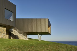 The funnel-like protrusion cantilevers over the hillside and is supported by angled pillars.