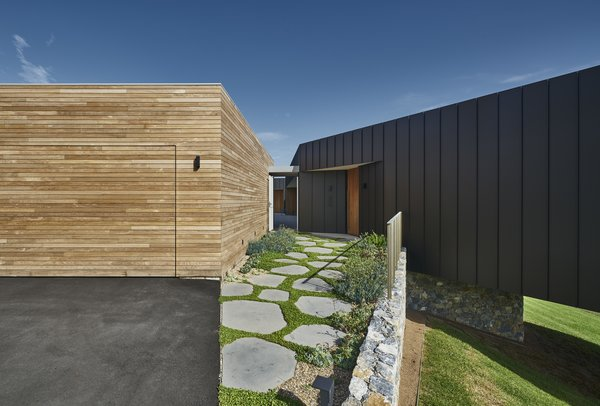 The property also features a wood-clad garage that sits adjacent to the residence.