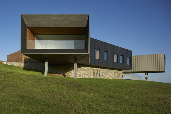 This full-height glazed wall and balcony look out toward dramatic framed views of the sea.