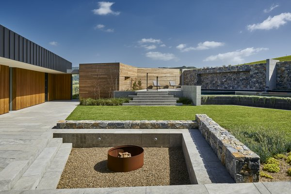 The home wraps around a courtyard that mixes a material palette of metal, wood, stone, and concrete.