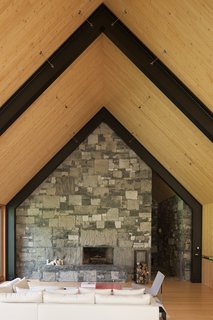 The use of stone carries over into the interiors to create a rustic, elegant, wood-burning fireplace.