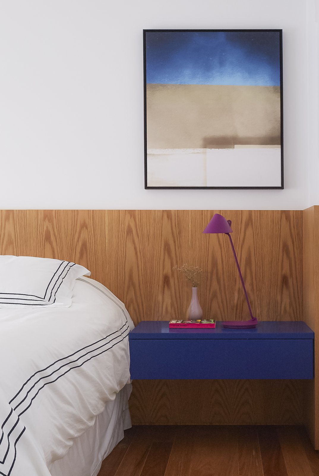 Bedroom, Medium Hardwood Floor, Bed, Table Lighting, Lamps, and Night Stands One of the bedrooms.  Photo 12 of 17 in Color Unites With Texture to Make This Brazilian Abode Appear Much Larger and Brighter
