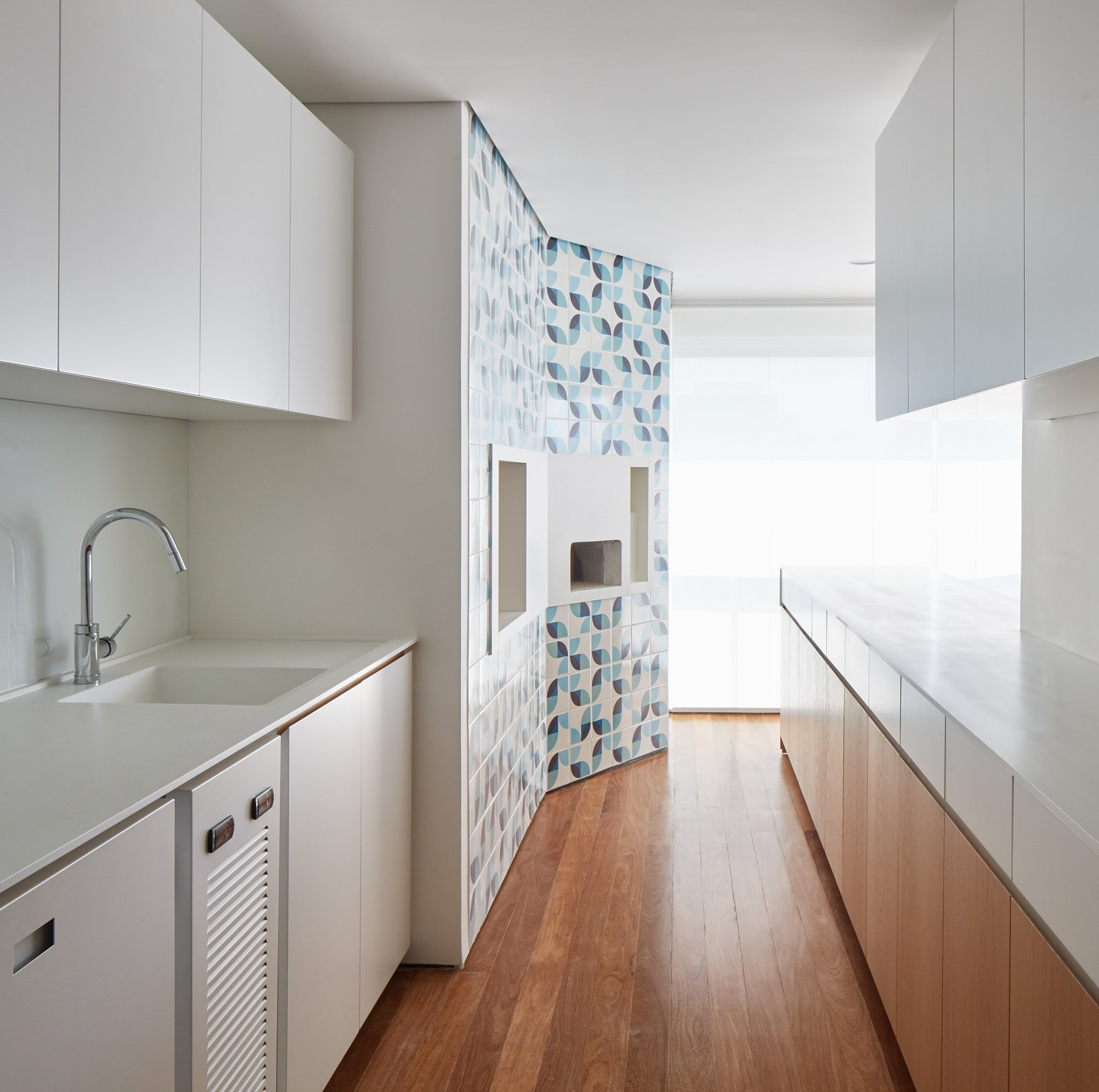 Kitchen, Medium Hardwood Floor, Wood Cabinet, White Cabinet, and Drop In Sink A  Photo 8 of 17 in Color Unites With Texture to Make This Brazilian Abode Appear Much Larger and Brighter