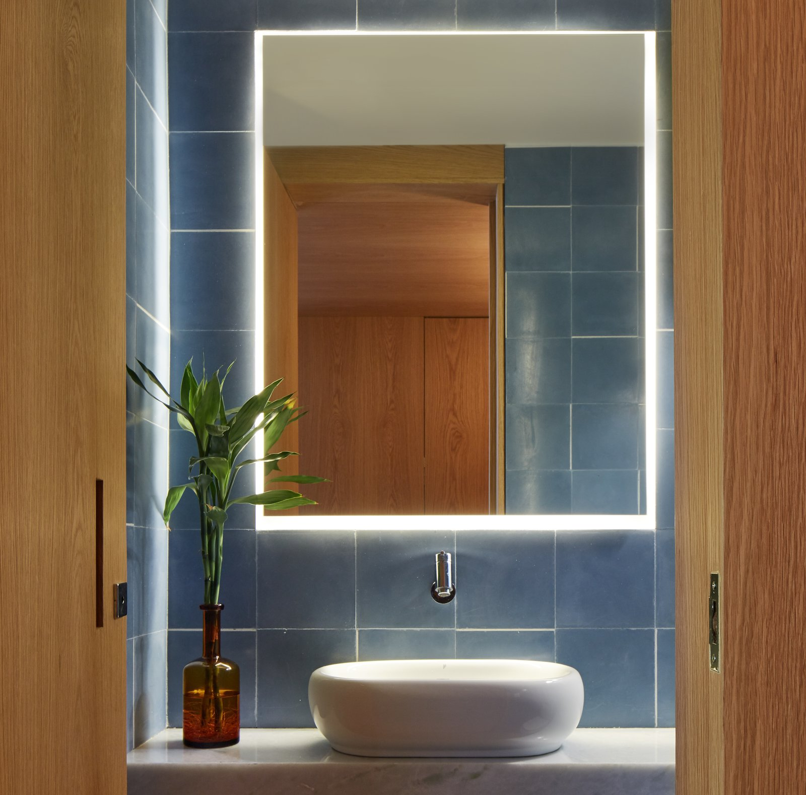 A deep earthy blue tile plays off the richness of the wood in this bathroom.