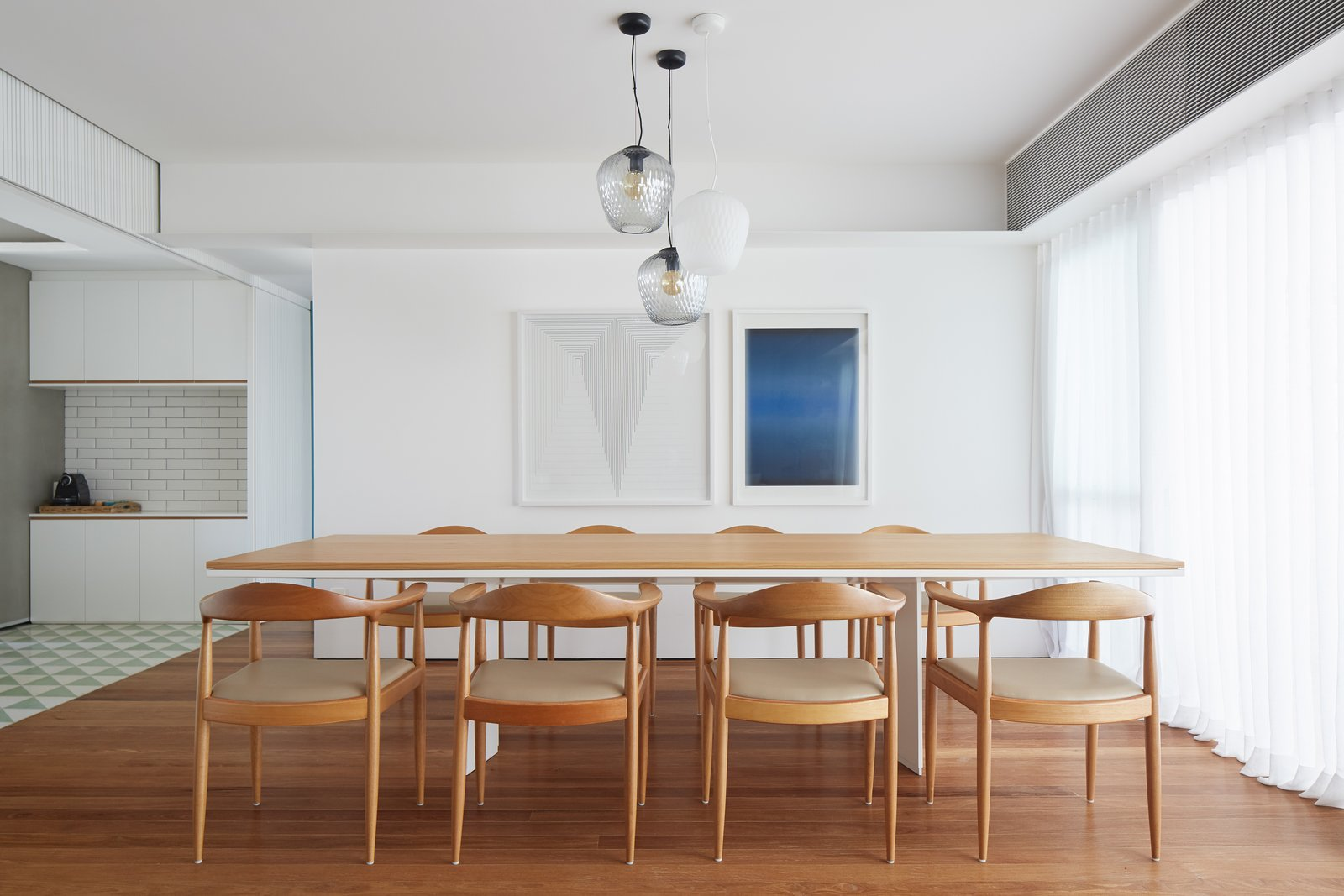 Dining Room, Pendant Lighting, Table, Medium Hardwood Floor, Rug Floor, and Chair T  Photo 5 of 17 in Color Unites With Texture to Make This Brazilian Abode Appear Much Larger and Brighter