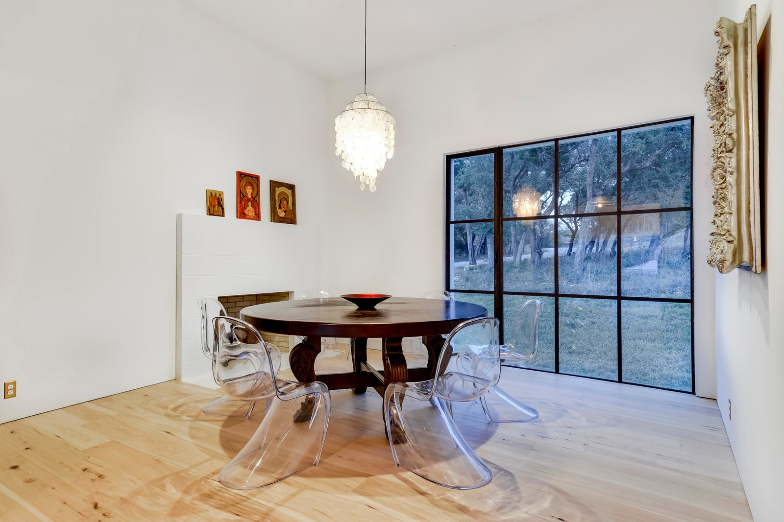 Dining Room, Table, Medium Hardwood Floor, Chair, Pendant Lighting, and Standard Layout Fireplace The dining area overlooks the yard.  Photo 7 of 22 in Own This Alluring Sculptural Abode in Austin For $3.1M