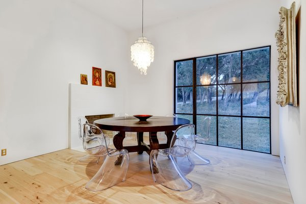 Medium Hardwood Floor and Pendant Lighting The dining area overlooks the yard.  Photo 7 of 22 in Own This Alluring Sculptural Abode in Austin For $3.1M