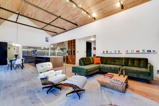 Own This Alluring Sculptural Abode in Austin For $3.1M - Photo 1 of 21 - The property is comprised of three distinct sculptural volumes. The simplified and abstracted white stucco forms and curvilinear roofs create a distinct composition within the landscape. In contrast, bold, tactile materials define the interiors. The home features an open plan kitchen, dining area, and living room, which all house wide plank hickory pecan floors and ceilings.