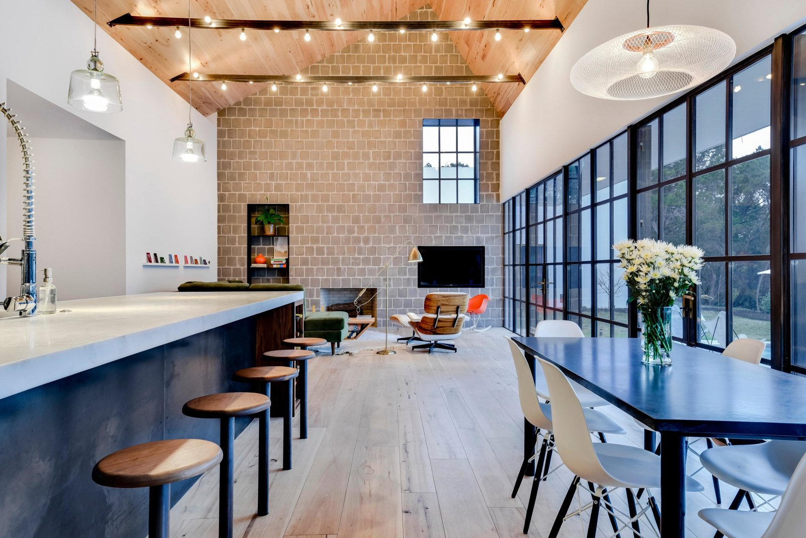 The craftsmanship integral to the experience of the house is evident in the welds of the custom steel windows, the tool marks of the waxed hot-rolled steel panel at the kitchen island, and the hand-turned walnut seats of the bar stools.