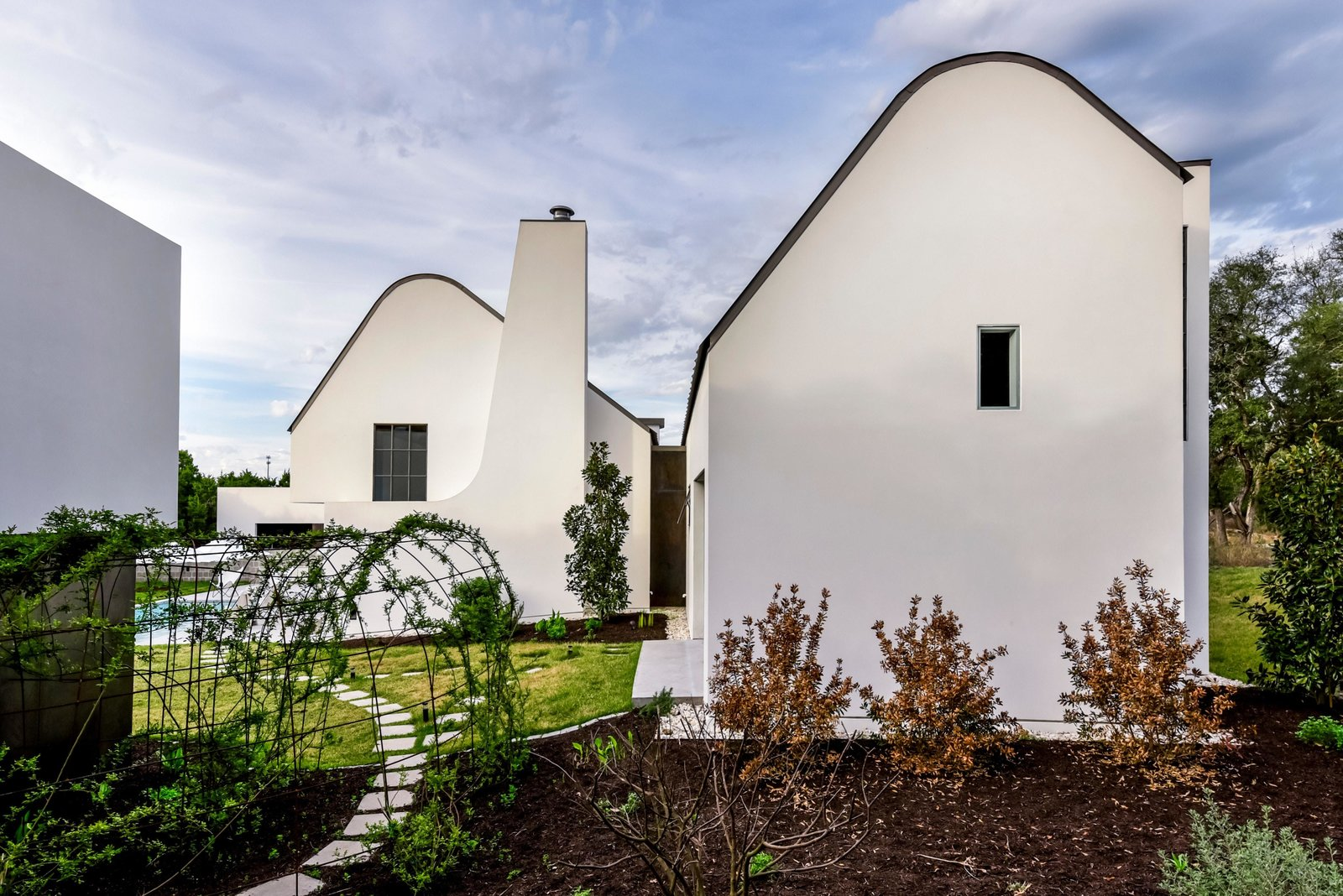 The stucco volumes create a sculptural composition within the landscape.