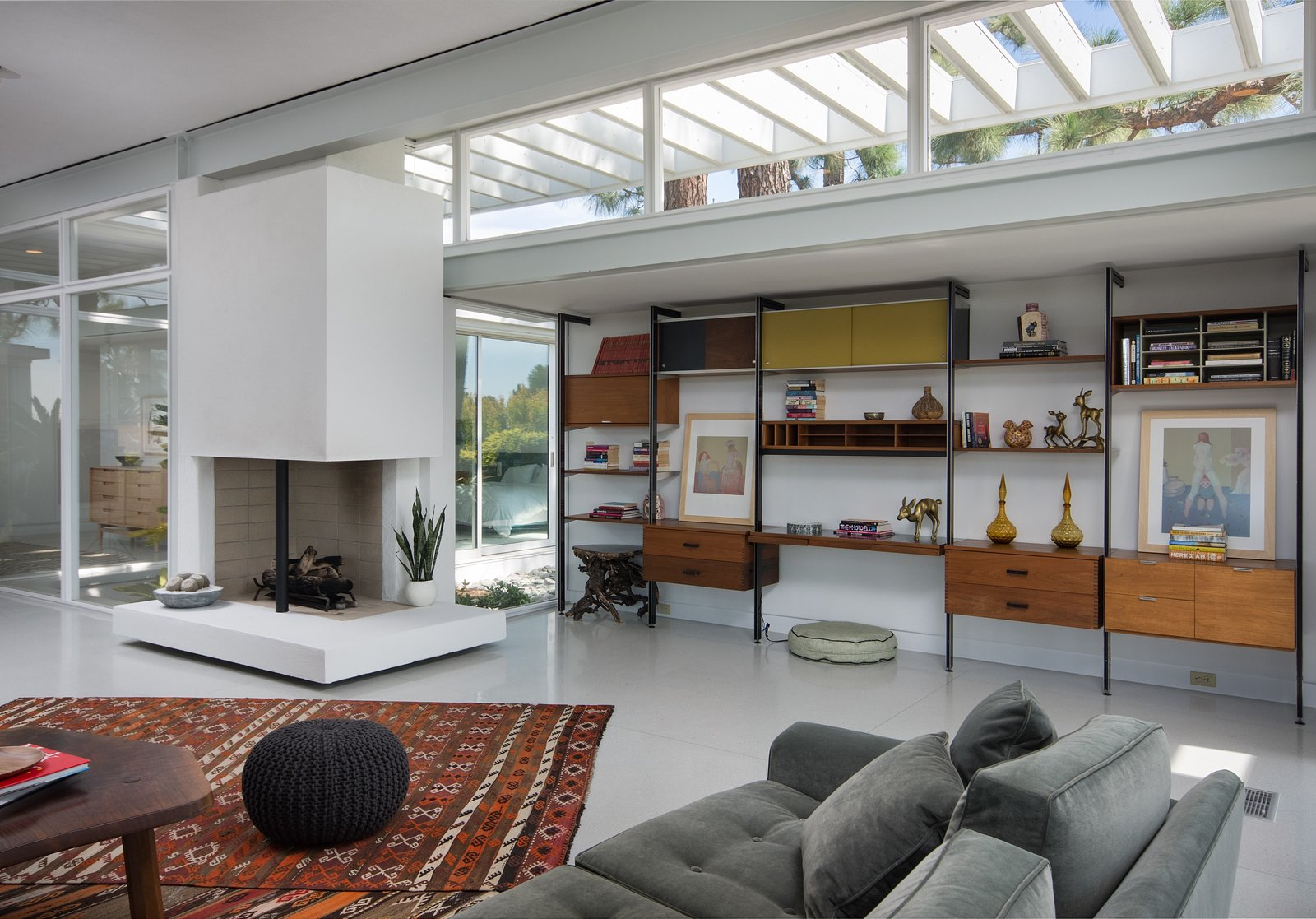 Living Room, Sofa, Corner Fireplace, Wood Burning Fireplace, Desk, Rug Floor, Shelves, Ottomans, and Coffee Tables The open-plan living room is anchored by a wood-burning two-sided fireplace.  Photo 3 of 8 in Rooney Mara Asks $3.45M For a Restored Midcentury Stunner in L.A.