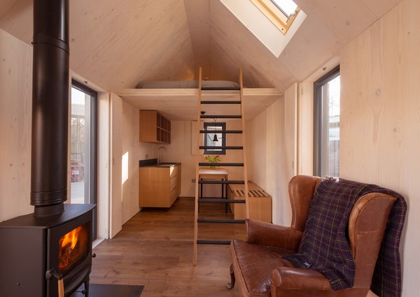 The compact interior space measures 129 square feet, with a built-in bed and space for a kitchenette, table, bench, shelves, and stove. The addition of a skylight helps keep the interiors bright.
