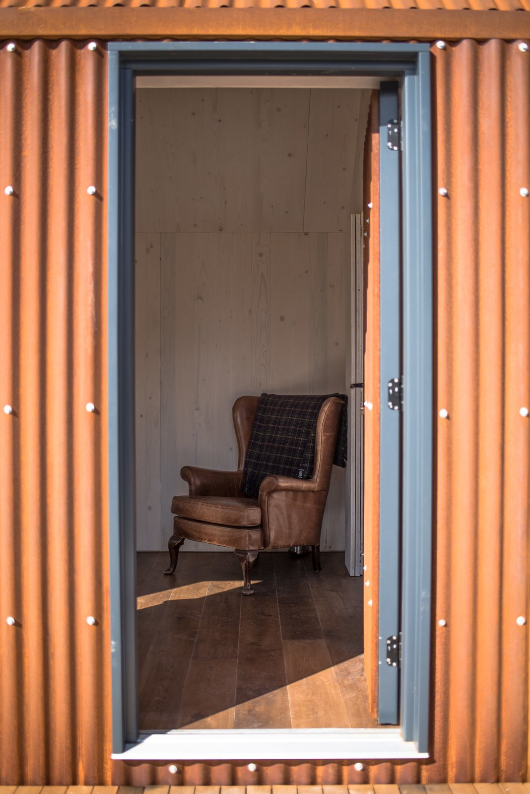 Doors, Swing Door Type, Exterior, and Metal The minimalist interiors are paneled in pin  Photo 7 of 12 in Go Off-Grid in This Prefabricated Cor-Ten Steel Cabin
