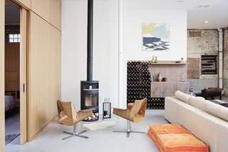 Two sculptural wooden chairs face a wood-burning stove.