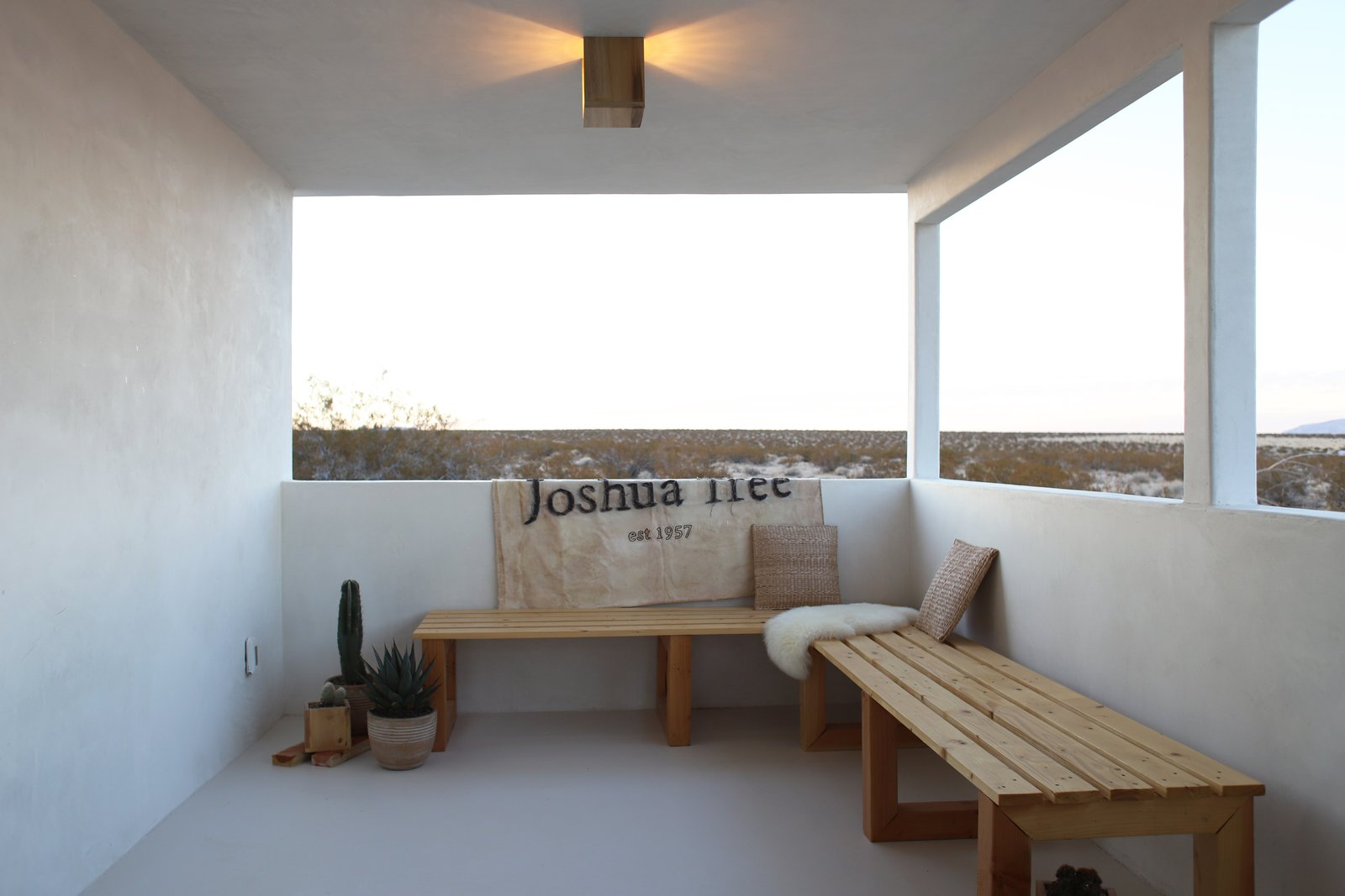 """Qn the opposite end of the covered patio the Smirkes built two long benches that overlook the open desert. The canvas is a flag they had made by Lindsay Smith of Makers Workshop that says, """"Joshua Tree Est. 1957"""" the year the original cabin was constructed."""