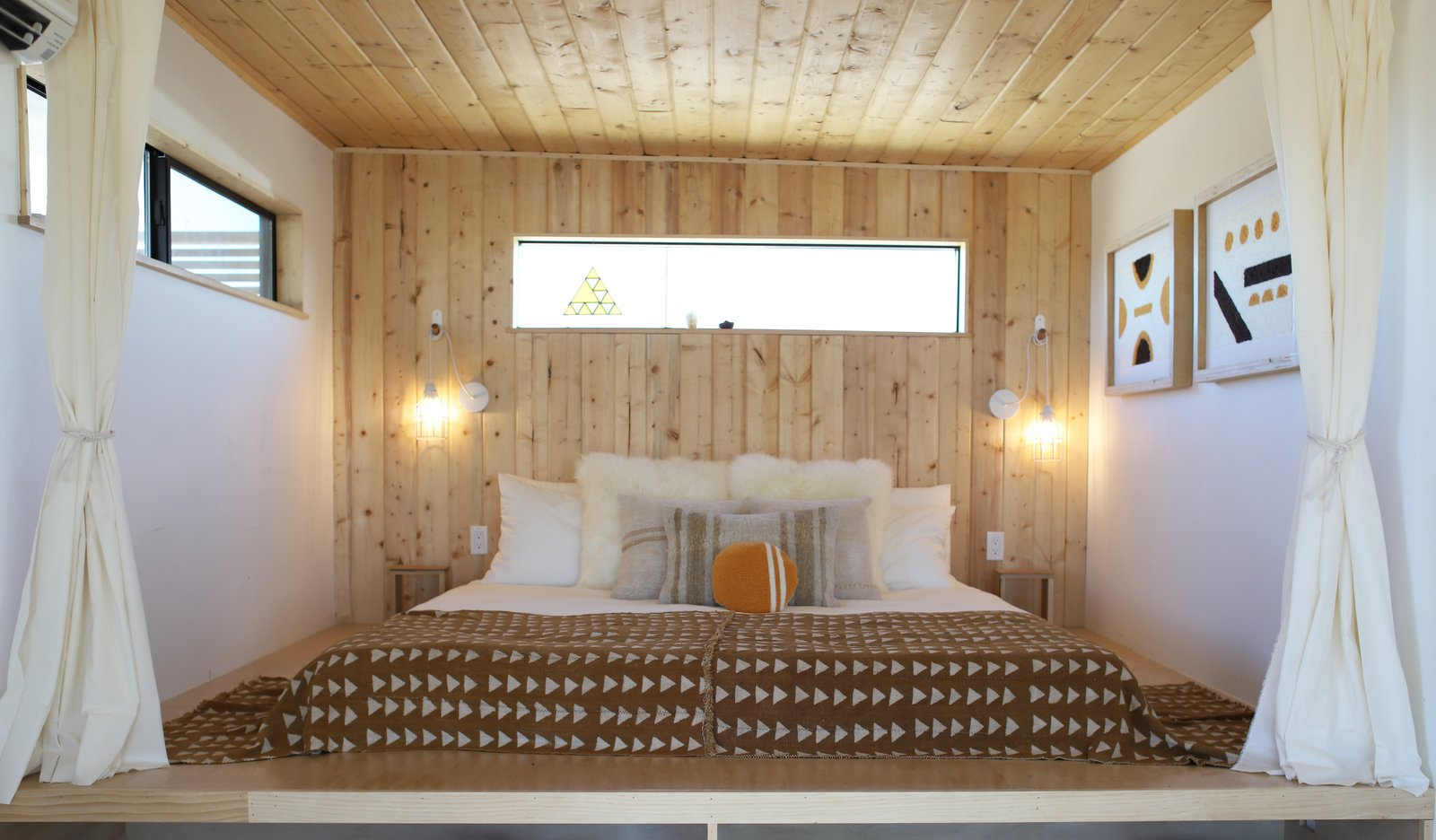 Wood paneling and a platform bed was a perfect solution for fitting a king-sized bed into a small space.