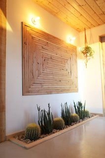 Brian created the wooden artwork from repurposed wood from the original structure. The glass front door even provides enough natural sunlight that the couple were able to plant an in-floor cactus garden. However, before they could get started, they had to remove a section of the concrete with a rented a jackhammer from Home Depot to accommodate the installation.