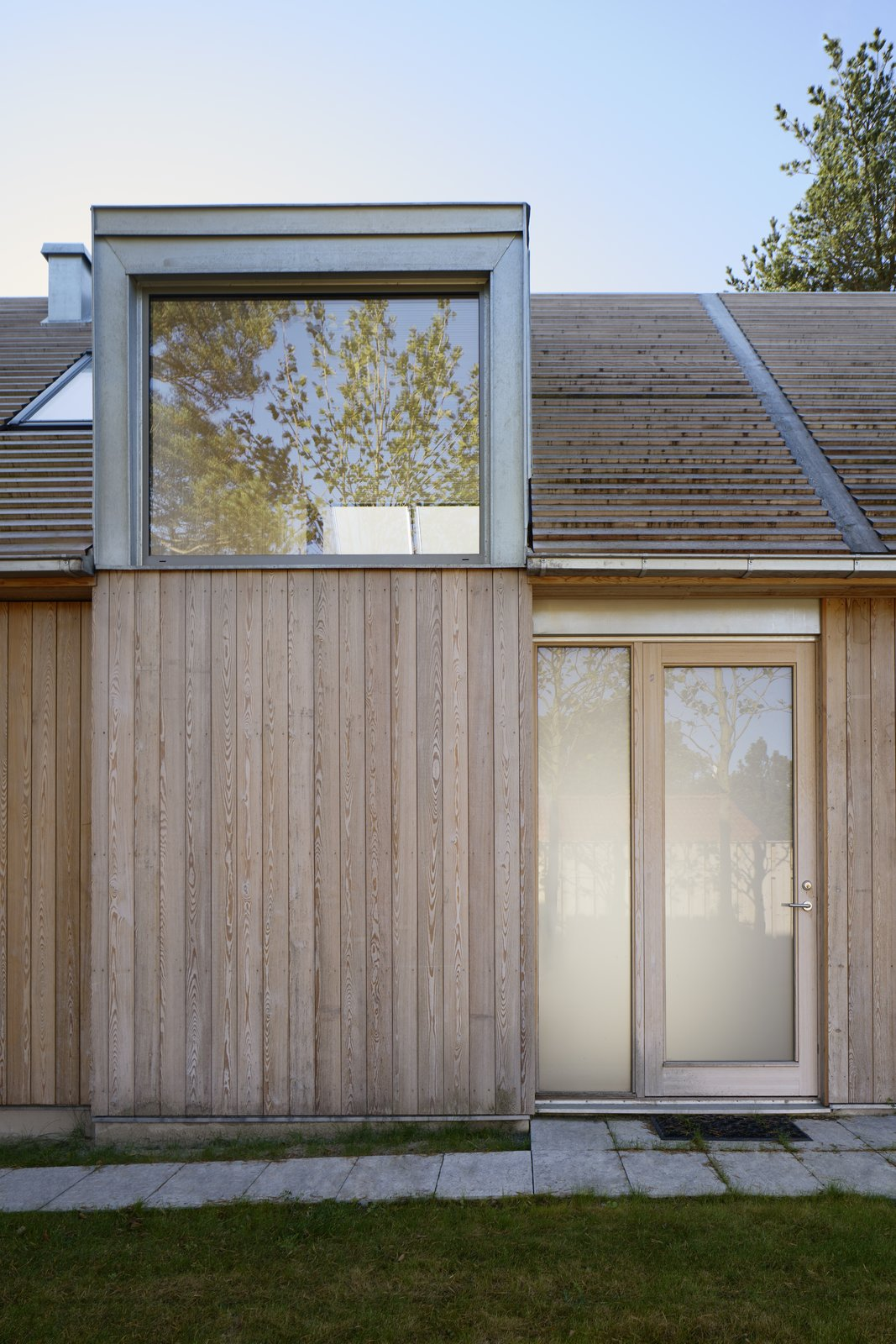The light-colored larch and expanses of glass give the home a natural vibe and help it integrate into its sylvan setting.