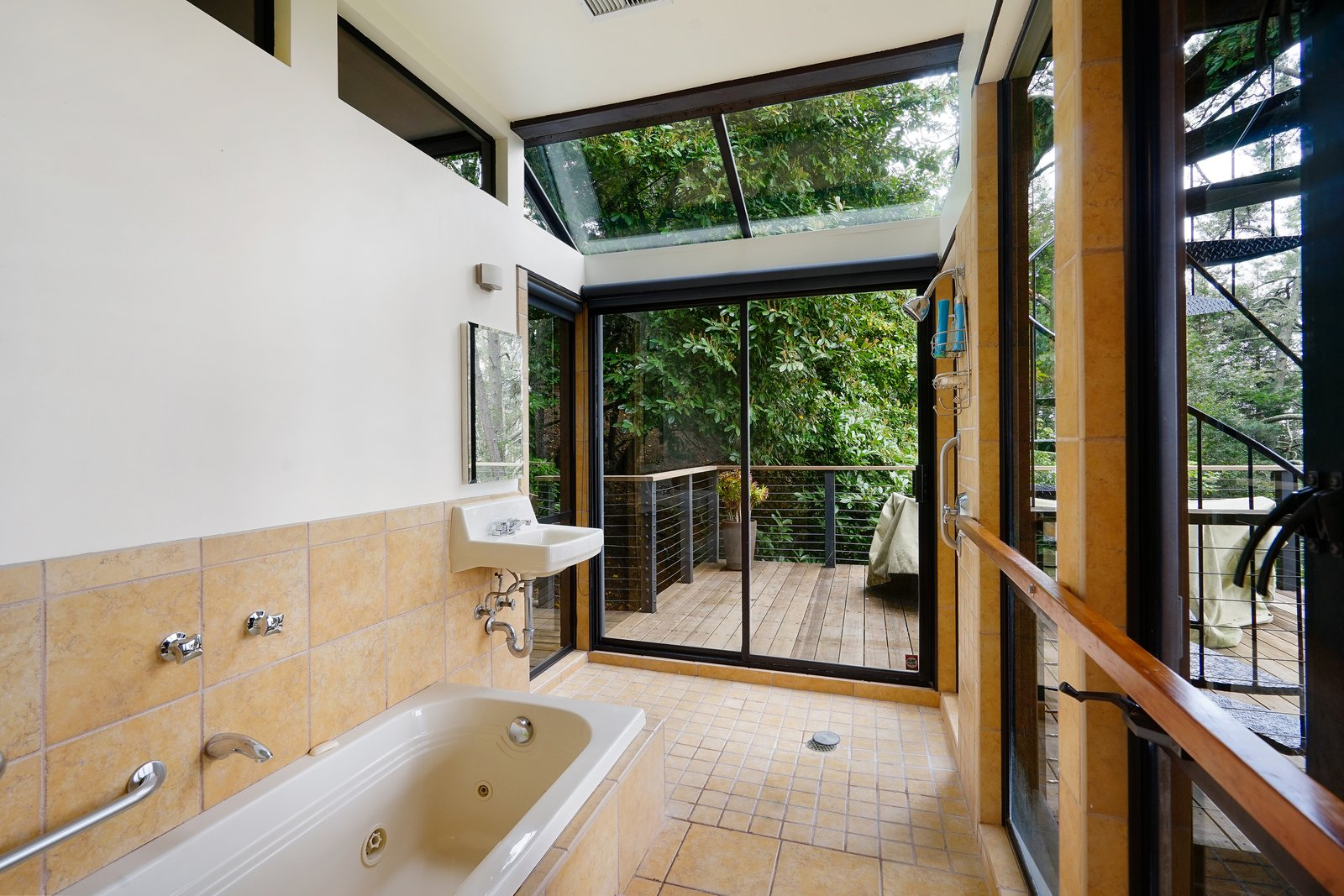 Bath Room, Drop In Tub, Ceramic Tile Floor, Ceramic Tile Wall, Wall Lighting, and Wall Mount Sink T  Photo 13 of 17 in This Knockout Midcentury in the Bay Area Will Run You $1.9M