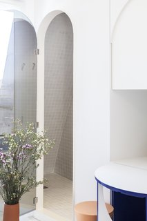 The compact bathroom is tucked away behind an arched-shaped mirror.