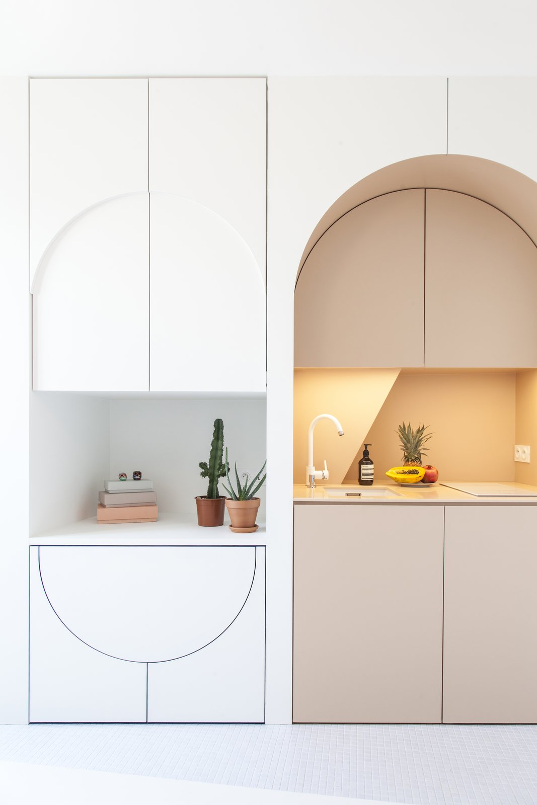 The clever design includes a hidden dining table, stools, and a fridge.
