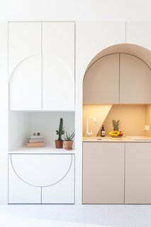 The redesign includes bespoke cabinetry which conceals a hidden dining table and stools, as well as a small fridge.