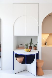 The tiny table with two stools pops out from the cabinetry.