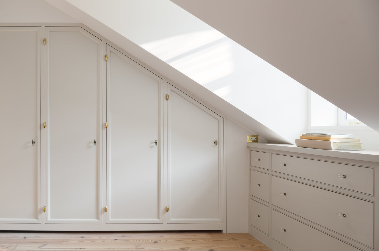 Custom millwork closets were added and lined with cedar and brass knobs that the owner found. Because of two dormers, the best use of space was to add drawers for additional storage.