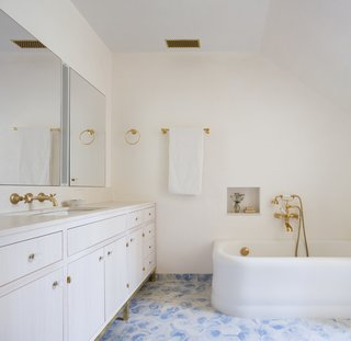 The bathroom in the master suite features a custom-made vanity and medicine cabinet. Tadelakt, a waterproof plaster surface, was used on the walls with Bulgarian limestone in the shower. The custom tiles were made by Haand Ceramics. The bathtub is a reclaimed piece with brass plumbing from Waterworks.