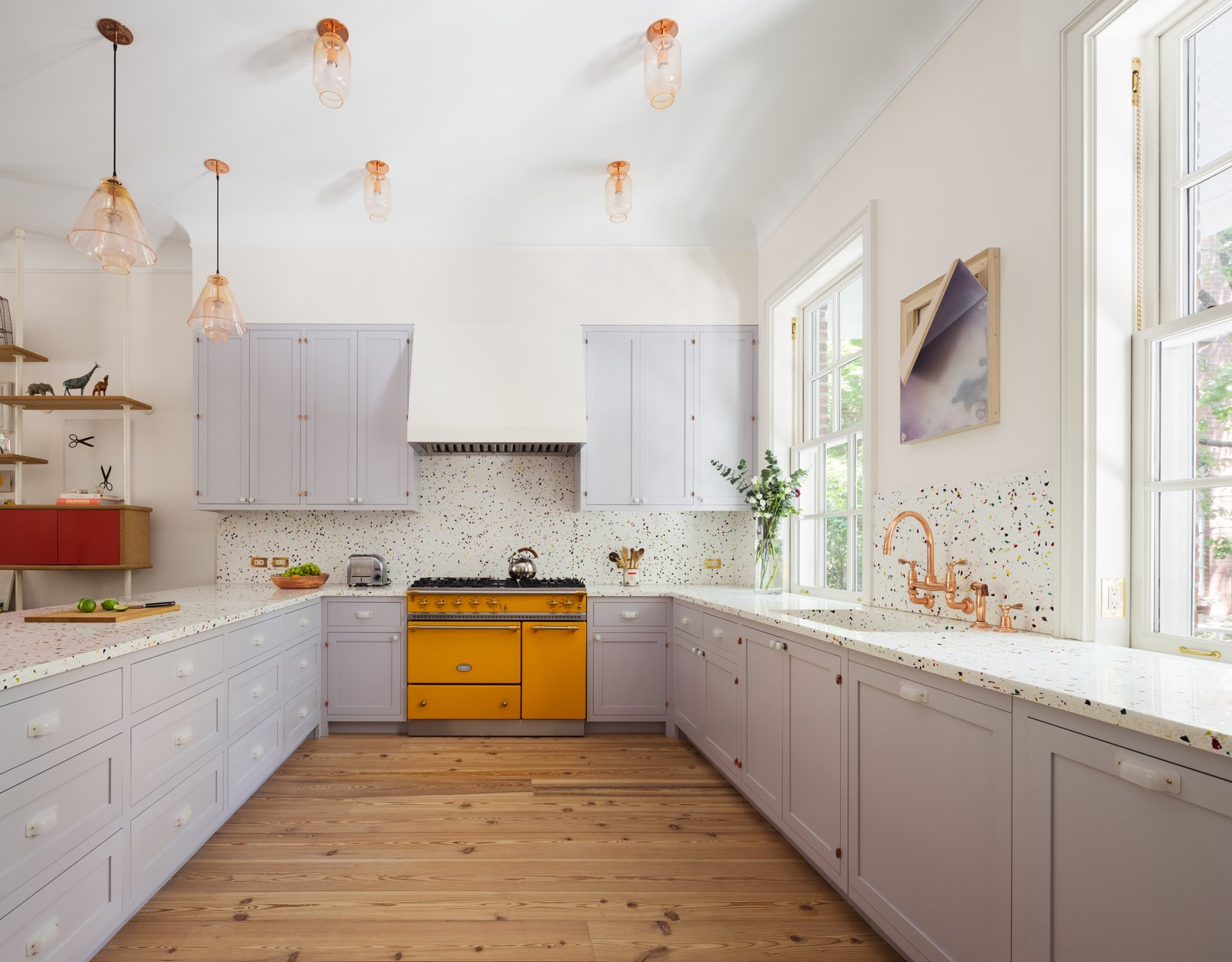 The kitchen features custom millwork with opal glass pulls, recycled glass terrazzo countertops and backsplash, copper plumbing, and a showstopping Lacanche range in Provence yellow.