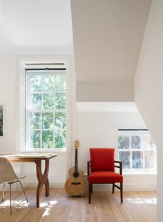 The study is punctuated by a red accent chair.