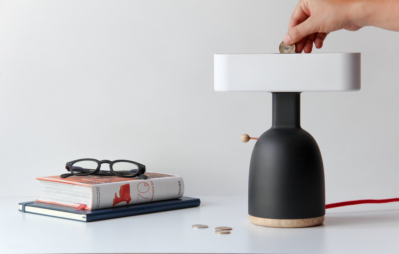 Currently, the Dina is just a prototype—the body and shade made with a 3D printer and the top and bottom lids made from natural ash wood. The interior features a mechanism that holds the coins and turns the light on by closing the electrical circuit.
