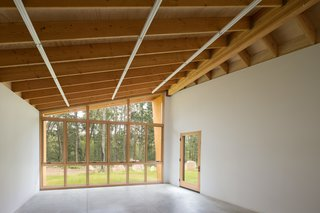 Inside the structure, wall space is prioritized with concealed plywood blocking to support hanging work.