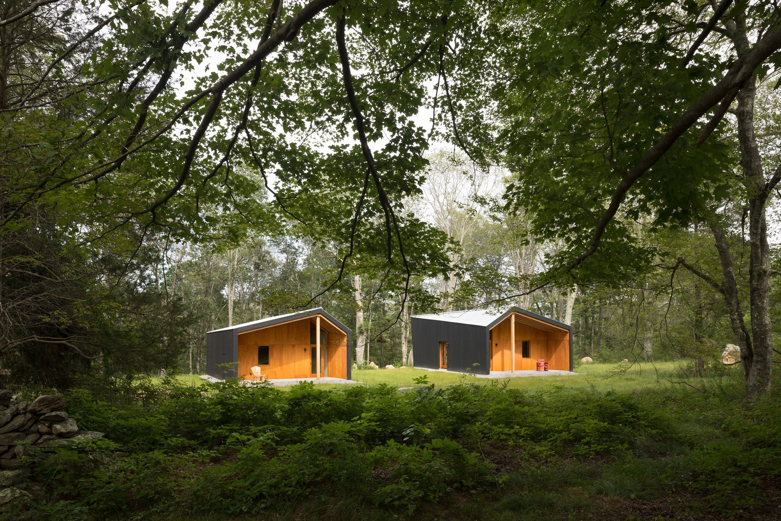 Sited to respect existing site features and topography, the two studios respectfully interact with the subtle tension of the shared space between them shaped by angled walls that frame and celebrate the surrounding countryside.