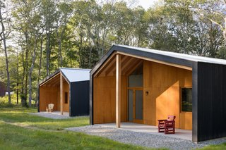 The dark stained cedar exteriors and galvanized metal roofs house bright, warm interiors.
