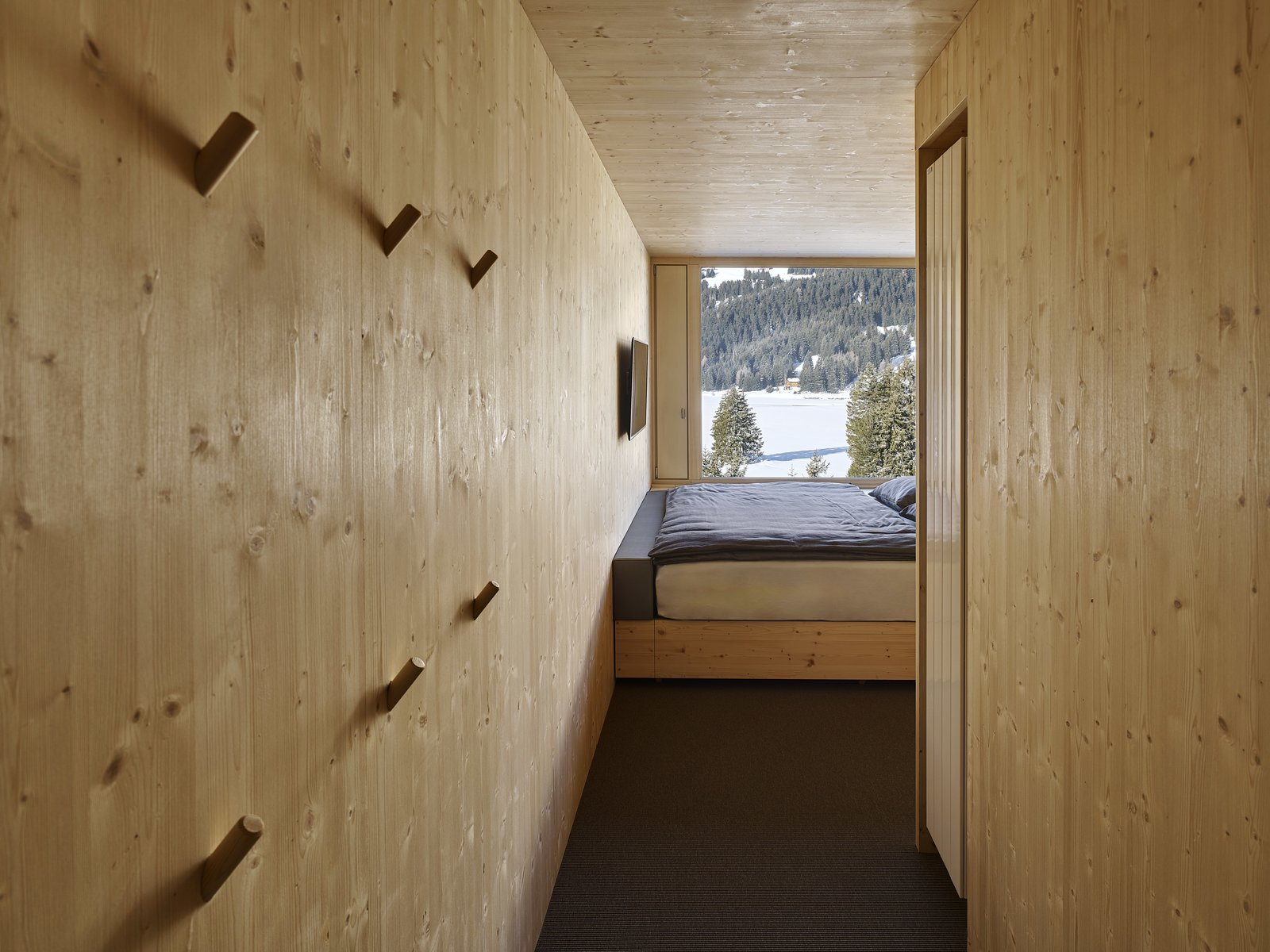 The ceilings, floors, and walls of the rooms are constructed from natural, unfinished plywood.