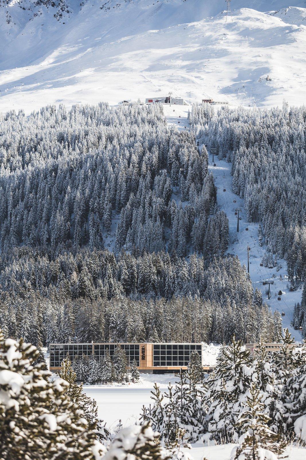 The modern ski chalet in its snowy alpine setting.