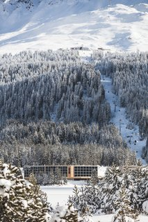 The modern ski chalet in its snowy alpine setting.