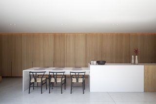 The light-filled kitchen is centered around a partially timber-clad island that matches the cabinetry.