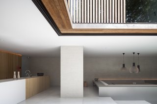 The open-plan living and dining area uses neutral colors and a minimalist material palette.