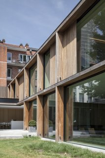 Timber, glass, and concrete compose the simple exterior of the structure.