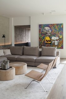 Recycled bricks that have been whitewashed play off the stone-colored sectional, tree-stump coffee tables, and leather chairs, while a dynamic work of art injects color and unexpected energy into the space.