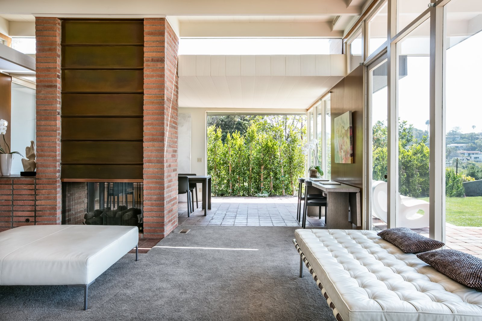 Living Room, Ottomans, Two-Sided Fireplace, Table, Wood Burning Fireplace, Carpet Floor, and Bench The high ceilings were designed to accommodate clerestory windows.  Photo 6 of 13 in Case Study House #18 in L.A. Hits the Market at $10M and Includes Plans From Tom Kundig